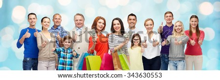 gesture, sale, shopping and people concept - group of smiling men, women and kids showing thumbs up and holding shopping bags with money over blue holidays lights background - stock photo