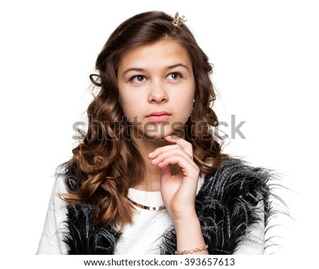 Gestures. Teenagers. Portrait of a young pensive girl in a light shirt and a fuzzy vest, isolated on white background - stock photo