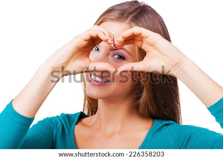 Gesturing finger heart. Beautiful young woman looking at camera and gesturing finger heart while standing isolated on white - stock photo