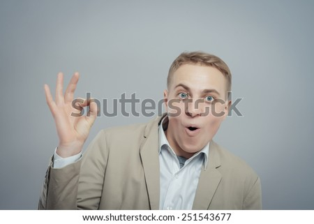 Gesturing OK sign. Cheerful young man in shirt gesturing OK sign while standing against grey background - stock photo