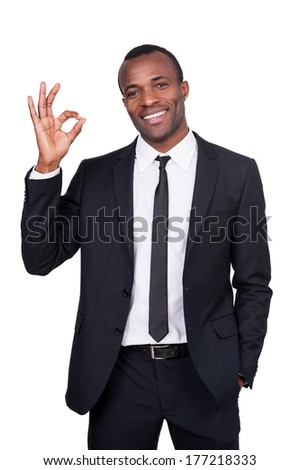Gesturing OK sign. Handsome young African man in full suit showing OK sign and smiling while standing isolated on white background  - stock photo
