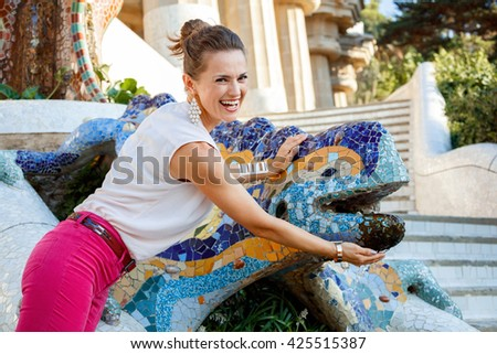 Get inspired by Park Guell in your next trip to Barcelona, Spain. Portrait of smiling young woman near multicolored mosaic dragon - stock photo