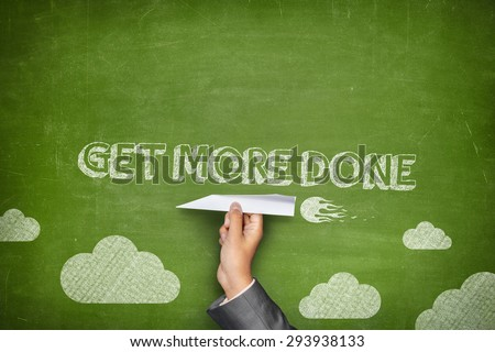Get more done concept on green blackboard with businessman hand holding paper plane - stock photo