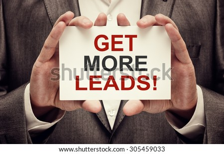 Get more leads! card in male hands - stock photo