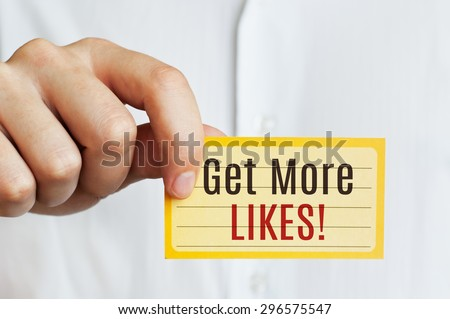 Get More Likes card in male hand - stock photo
