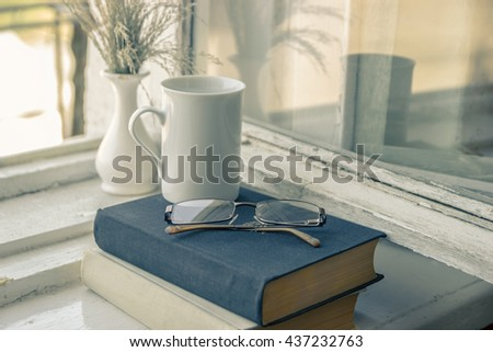 Getting an education - the road to knowledge. Reading books - the path to wisdom. Glasses, vase, cup, black and white books. - stock photo