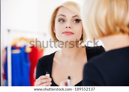 Getting ready to the night out. Beautiful young blond hair woman doing make-up and smiling while looking at the mirror - stock photo
