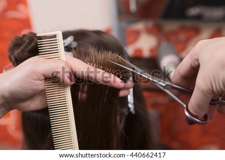 Getting rid of those split ends. Cropped shot of female hairdresser cutting client's hair with scissors at beauty salon. - stock photo