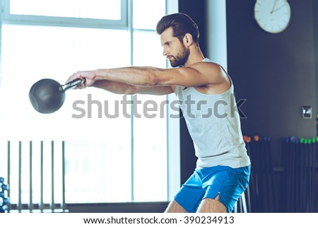 Getting stronger every day. Side view of young handsome man in sportswear working out with kettle bell at gym - stock photo