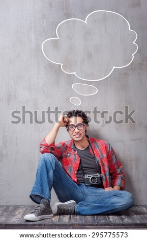 Getting the best photos. Handsome young Afro-American hipster with camera leaning on the grey wall. Bubble with copy space. - stock photo