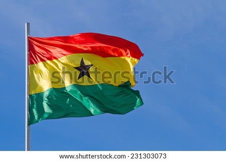 Ghana flag is waving in front of blue sky  - stock photo