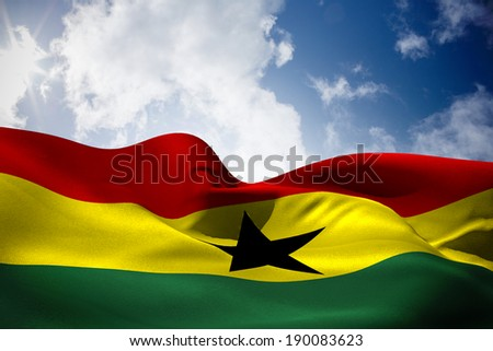 Ghana flag waving against bright blue sky with clouds - stock photo