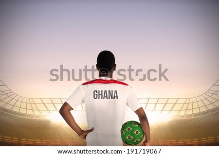 Ghana football player holding ball against large football stadium under blue sky - stock photo