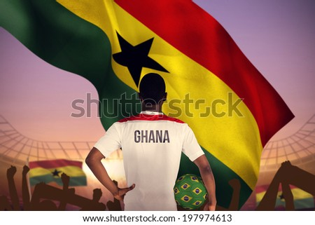 Ghana football player holding ball against large football stadium under purple sky - stock photo