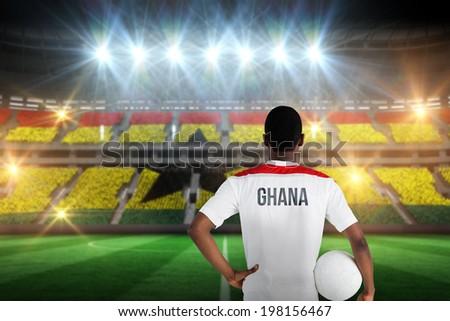 Ghana football player holding ball against stadium full of ghana football fans - stock photo