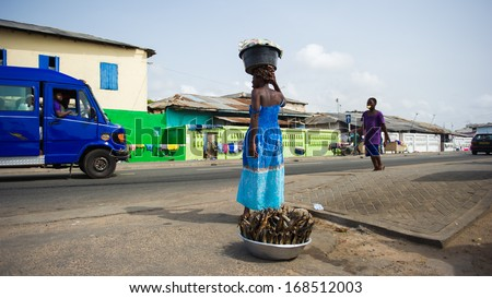 GHANA - MARCH 2, 2012: Unidentified Ghanaian woman sells fish near the road in Ghana, on March 2nd, 2012. People in Ghana suffer from poverty due to the slow development of the country - stock photo