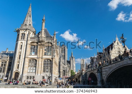 Ghent, Belgium - Sep 26, 2015: Ghent. Image of people enjoing Ghent, Belgium during daylight. People sitting on the edge of canal bridge in Leie river - stock photo