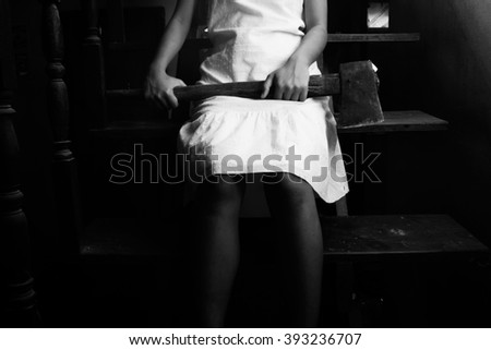 Ghost girl in haunted house holding an axe,Mysterious girl in white dress sitting on stairway in abandon house - stock photo