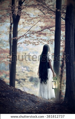 Ghost of a girl with lantern in the autumn forest. - stock photo
