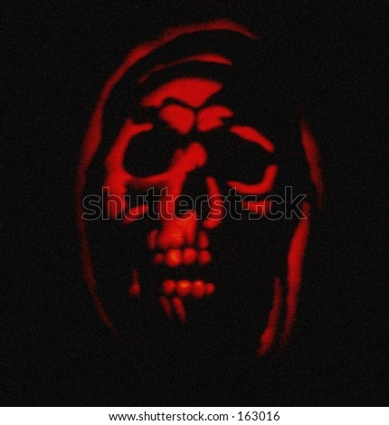 Ghostly image in red, carved Halloween pumpkin - stock photo
