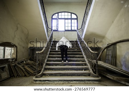 Ghostly woman in abandoned house staircase - stock photo