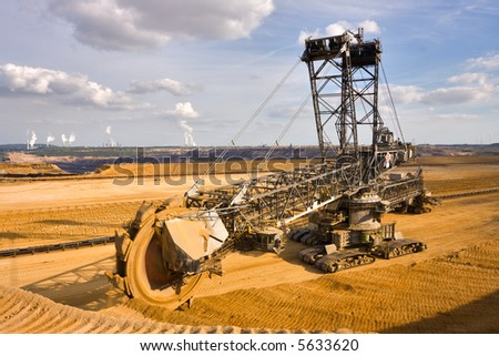 Giant bucket wheel excavator taking away the layers of ground before digging the brown coal. Largest open pit lignite mine in Europe. Power stations at horizon transform the coal to electricity. - stock photo