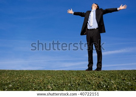 Giant businessman with arms outstretched on grassy hillside - stock photo