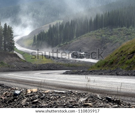 Giant dump truck makes it way down from an open pit coal mine in the Canadian Rocky Mountains. - stock photo