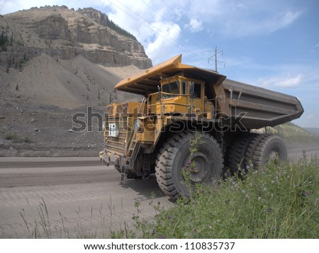 Giant dump truck makes it way into the Canadian Rocky Mountains near an open pit coal mine - stock photo
