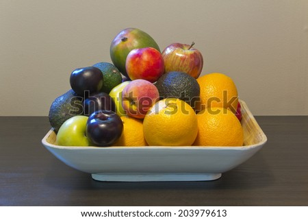 Giant fruit bowl with plum, avocado, orange, peach, nectarine, apple, and mango - stock photo