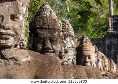 Giant guards in Angkor Thom front gate in Cambodia - stock photo