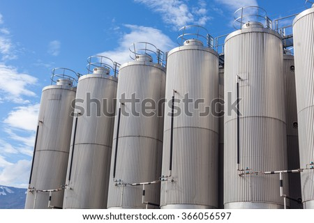 Giant industrial tanks on the bright blue sky background - stock photo