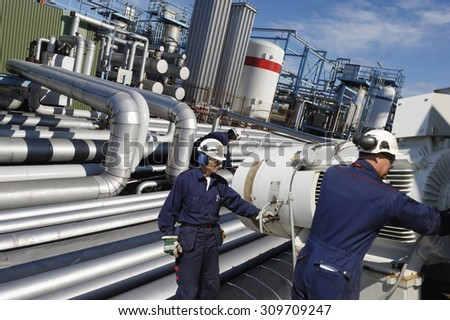 giant pipeline construction, engineer checking for leaks, safety precautions - stock photo