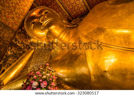 Giant statue of golden reclining lord Buddha at Wat Pho temple in Bangkok, Thailand. - stock photo