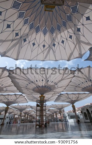 Giant umbrellas at Nabawi Mosque compound in Medina, Kingdom of Saudi Arabia. Nabawi mosque is the second holiest mosque in Islam. - stock photo