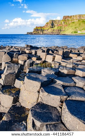 Giants Causeway, unique geological hexagonal formations of volcanic basalt rocks and cliffs on Atlantic coast in County Antrim, Northern Ireland, in sunset light. UNESCO World Heritage site - stock photo