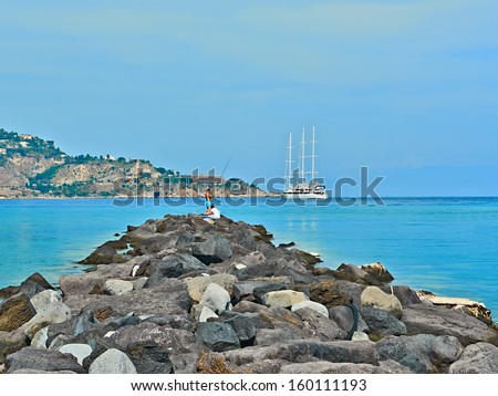 Giardini Naxos, Sicily, Italy - SEPTEMBER 10, 2013: Fishermen on the Ionian Sea near Taormina. Taormina is a small town on the east coast of the island of Sicily, Italy.  - stock photo
