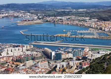 Gibraltar city and bay, airport runway and La Linea de la Concepcion town in Spain. - stock photo