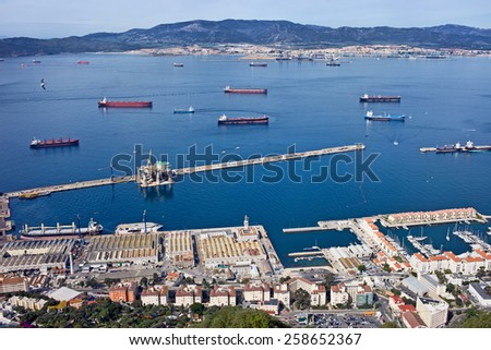 Gibraltar quay from above, Algeciras city in Spain on the horizon, cargo ships on bay waters - stock photo
