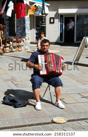 GIBRALTAR, UK - APRIL 20 2009 - Piano accordionist playing for money in Main Street, Gibraltar, United Kingdom, Western Europe, April 20, 2009. - stock photo