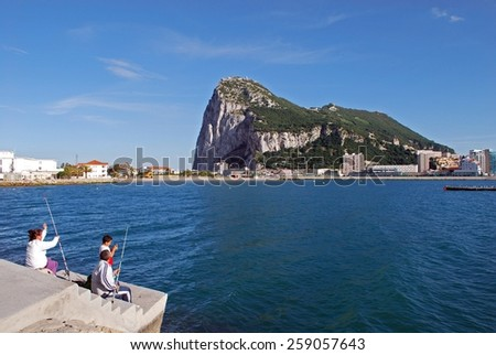 GIBRALTAR, UK - APRIL 20, 2009 - The rock seen across the bay from Spain with a family fishing in the foreground, Gibraltar, United Kingdom, Western Europe, April 20, 2009. - stock photo