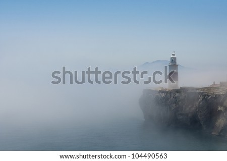 Gibraltars lighthouse at Europa Point standing in the mist with Africa in the distance. - stock photo