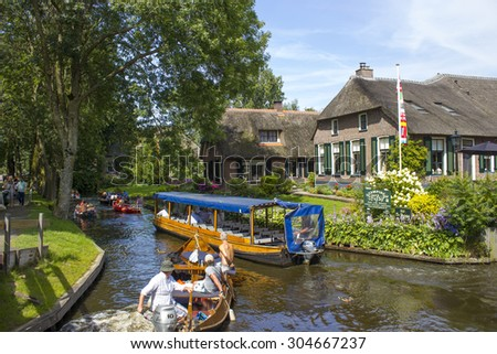 """GIETHOORN, NETHERLANDS - AUGUST 05, 2015: Unknown visitors in the sightseeing boating trip in a canal in Giethoorn. The beautiful houses and gardening city is know as """"Venice of the North"""".  - stock photo"""