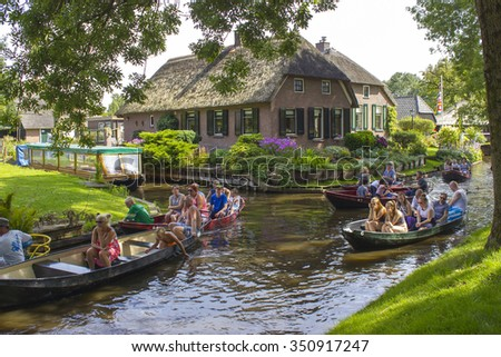 "GIETHOORN, NETHERLANDS - AUGUST 05, 2015: Unknown visitors in the sightseeing boating trip in a canal in Giethoorn. The beautiful houses and gardening city is know as ""Venice of the North"".  - stock photo"