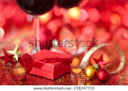 Gift and wine for holidays against blurred lights. - stock photo