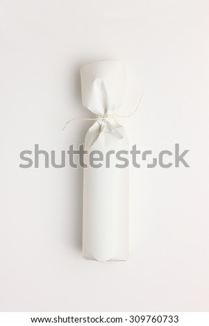 Gift bottle wrapped in white paper on white background - stock photo