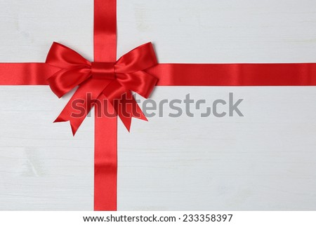 Gift bow and red ribbon for gifts on a wooden background - stock photo