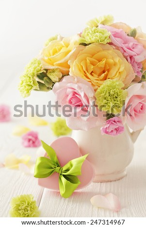 gift box and bouquet of flowers in a vase - stock photo