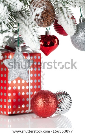 Gift box and christmas decor under snowy fir tree. Isolated on white background - stock photo