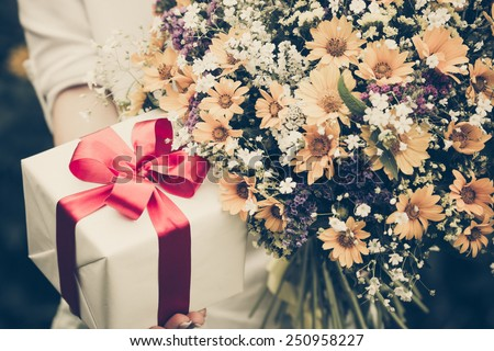 Gift box and flowers in hands against spring background. Family holiday concept. Mothers day - stock photo